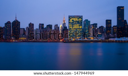 the buildings of manhattan at night in front of east river