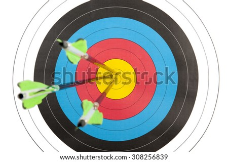 The bull's eye of an archery target hit by three arrows