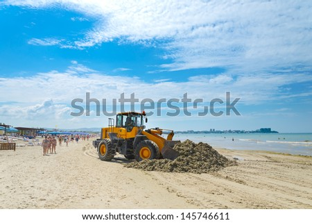 The bulldozer cleans dirt on a beach after a storm - stock photo
