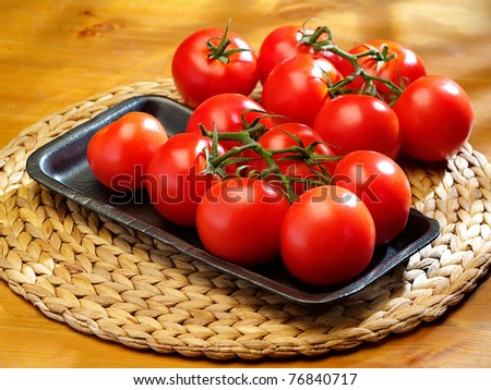 The bunch of  tomatoes on a table