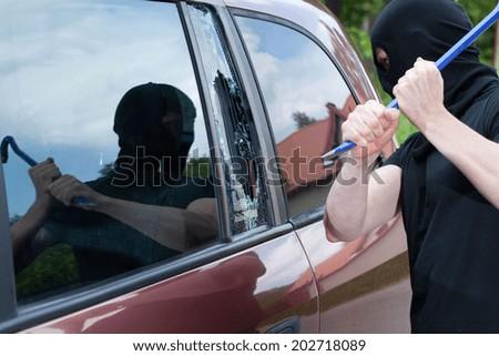 The burglar smash the glass in the window of the car - stock photo