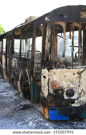 the burned-down public transport on a city road - stock photo