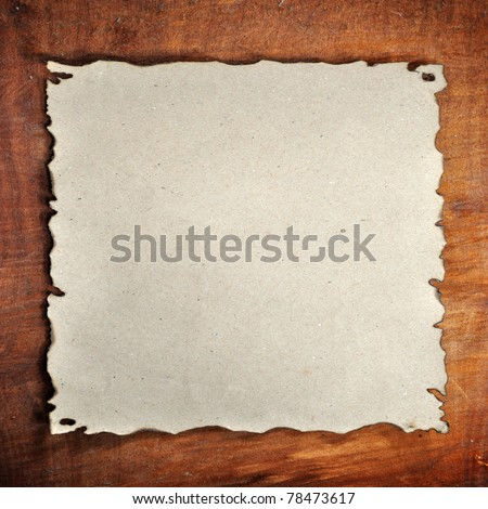 the burned paper on the wood background - stock photo