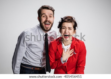 The business man and woman laughing on a gray background - stock photo