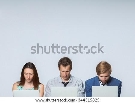 The business team working on laptops in the office on gray background - stock photo