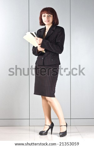 The business woman with folders in hands at a wall