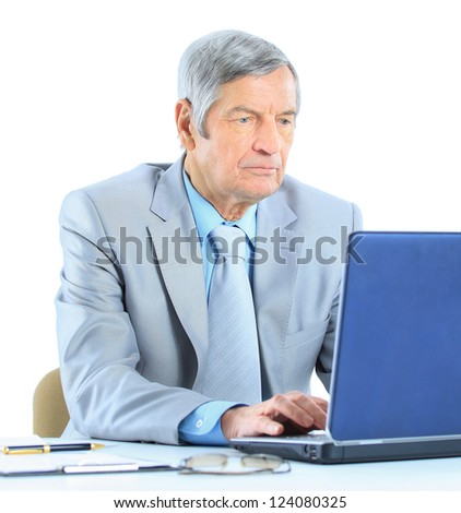 The businessman at the age of works for the laptop. Isolated on a white background.