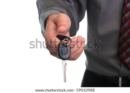 The businessman in a grey shirt and a tie stretches a car key. - stock photo