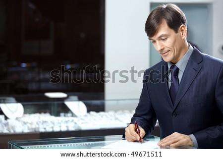 The businessman in a suit signs papers - stock photo