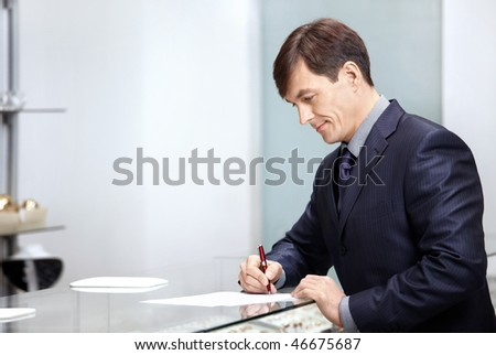 The businessman in a suit signs the important documents - stock photo