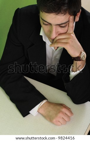 The businessman in a suit sits at a table and thinking about business - stock photo