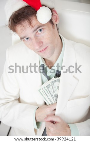 The businessman in a white suit and a Christmas cap hides money in a pocket