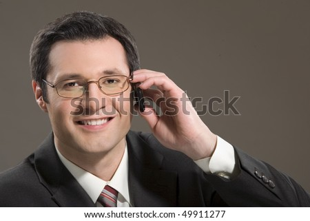 The businessman in points smiles and speaks by a mobile phone - stock photo