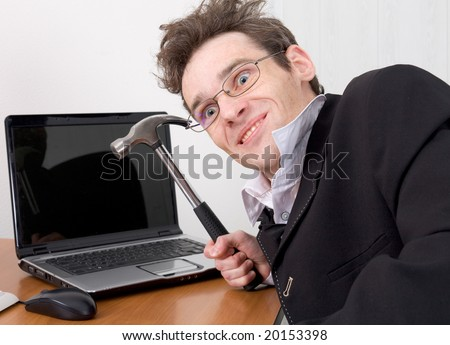 The businessman in spectacles gone mad with a hammer in a hand - stock photo