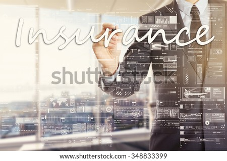 the businessman in the office is writing on the transparent board: Insurance - stock photo