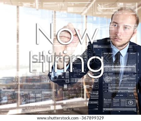 the businessman in the office is writing on the transparent board: Now Hiring - stock photo