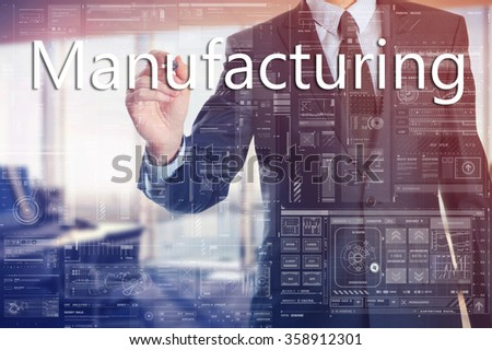 the businessman in the office is writing on the transparent board words associated with the manufacturing: Manufacturing - stock photo