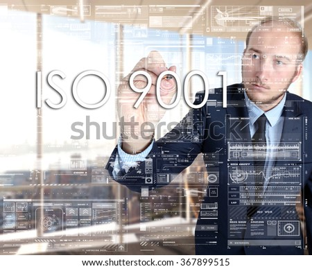 the businessman in the office is writing on the transparent board words associated with the manufacturing: ISO 9001 - stock photo