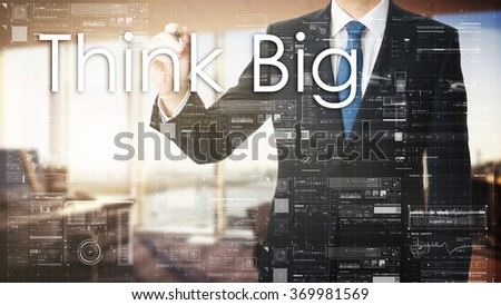 the businessman in the office is writing on the transparent board words associated with the employment: Think Big - stock photo