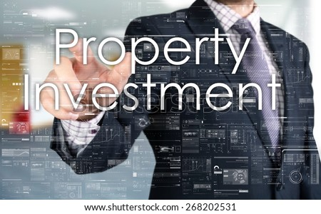 the businessman is choosing Property Investment from touch screen - stock photo