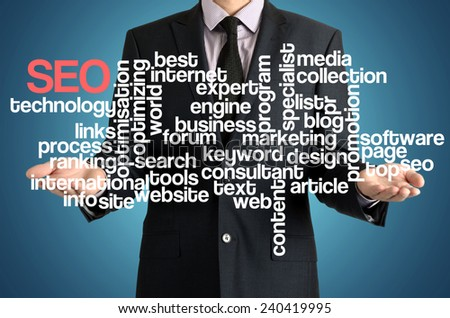 the businessman is presenting the cloud of connected words with: SEO - stock photo