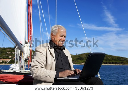 The businessman is working during the vacation on a sailboat with a lovely beach in the background. - stock photo