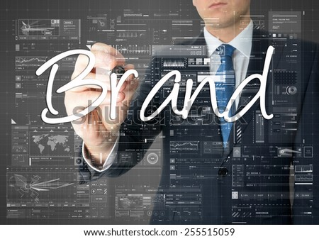 the businessman is writing Brand on the transparent board with some diagrams and infocharts - stock photo