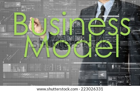 the businessman is writing Business Model on the transparent board with some diagrams and infocharts with the dark elegant background - stock photo