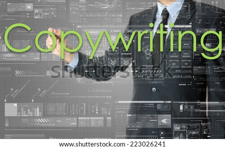 the businessman is writing Copywriting on the transparent board with some diagrams and infocharts with the dark elegant background - stock photo