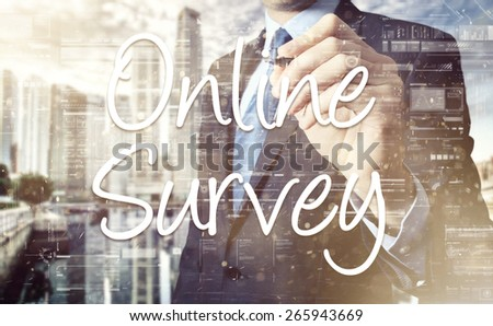 the businessman is writing Online Survey on the transparent board with some diagrams and infocharts  - stock photo