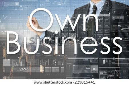 the businessman is writing Own Business on the transparent board with some diagrams and infocharts with the city in the background - stock photo
