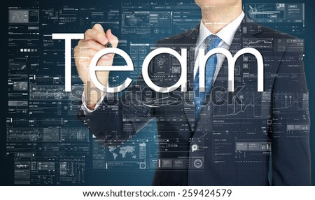 the businessman is writing Team on the transparent board with some diagrams and infocharts with the dark elegant background - stock photo