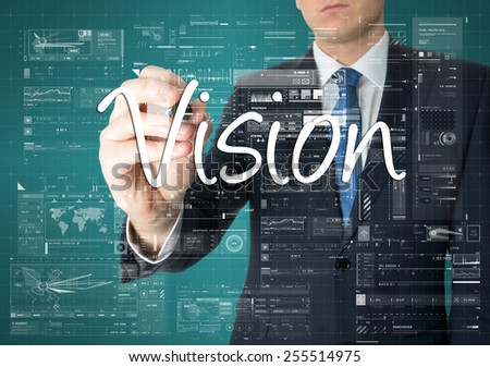 the businessman is writing Vision on the transparent board with some diagrams and infocharts - stock photo
