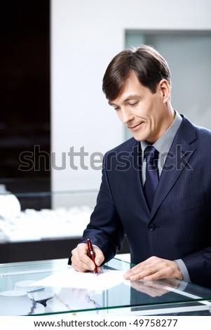 The businessman of average years signs papers - stock photo