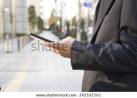 The businessman operating smart phone - stock photo