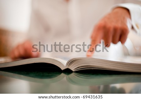 The businessman points a finger in the book on a light dim background - stock photo