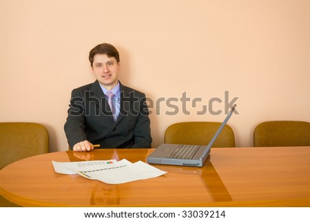 The businessman sits at a table with the laptop - stock photo