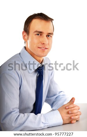 The businessman sitting on the desk in office - stock photo