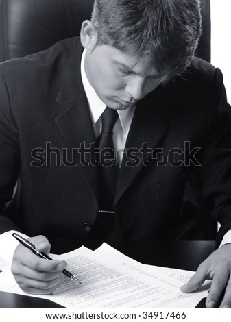 The businessman the studying contract before the signature. Monochrome photo. - stock photo