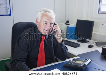 The businessman uses the telephone to communicate with clients in the office. - stock photo