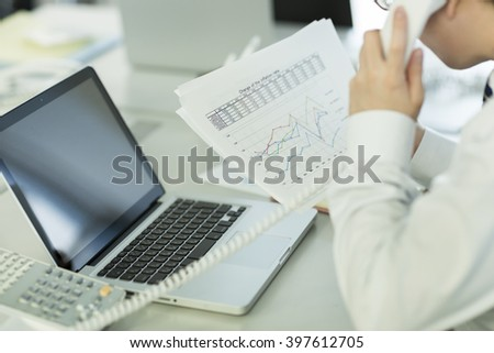 The businessman who calls while seeing a document - stock photo