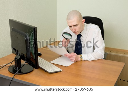 The businessman with a magnifier in a hand on a workplace - stock photo