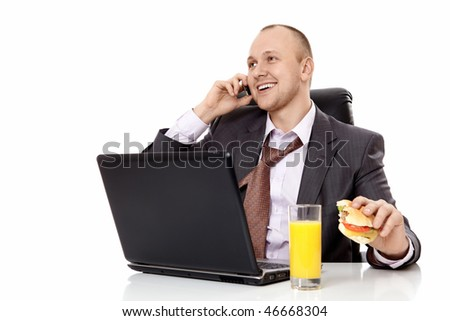 The businessman with the laptop and a hamburger