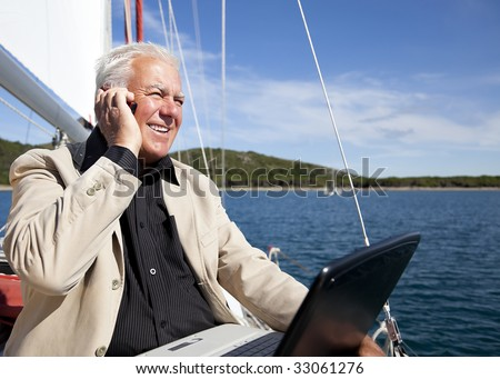 The businessman working happily with the computer and mobile phone while on the vacation on the sailboat. - stock photo