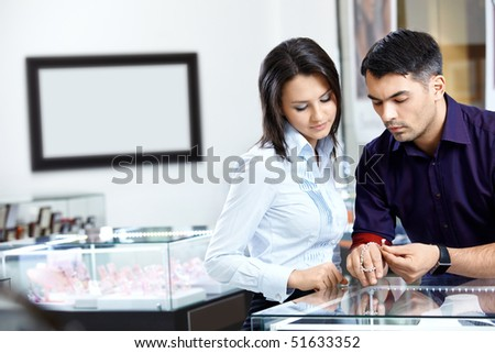 The buyer and the seller choose a jewel - stock photo