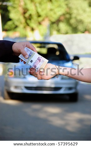 The buyer transfers a pack of money for the car - stock photo