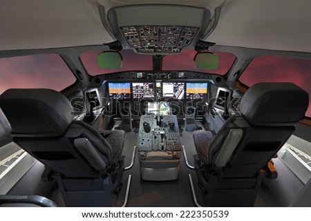 The cabin of the modern passenger airliner, nobody, autopilot, cloudy sunset sky outside the window - stock photo