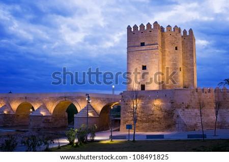 The Calahorra Tower (Spanish: Torre de la Calahorra) and The Roman Bridge at dusk in Cordoba, Spain. - stock photo