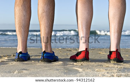 The calves and feet with shoes of two men on the beach in late afternoon sunlight - stock photo