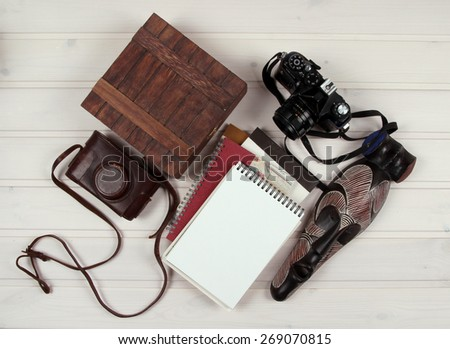 The camera and mask on a wooden texture - stock photo